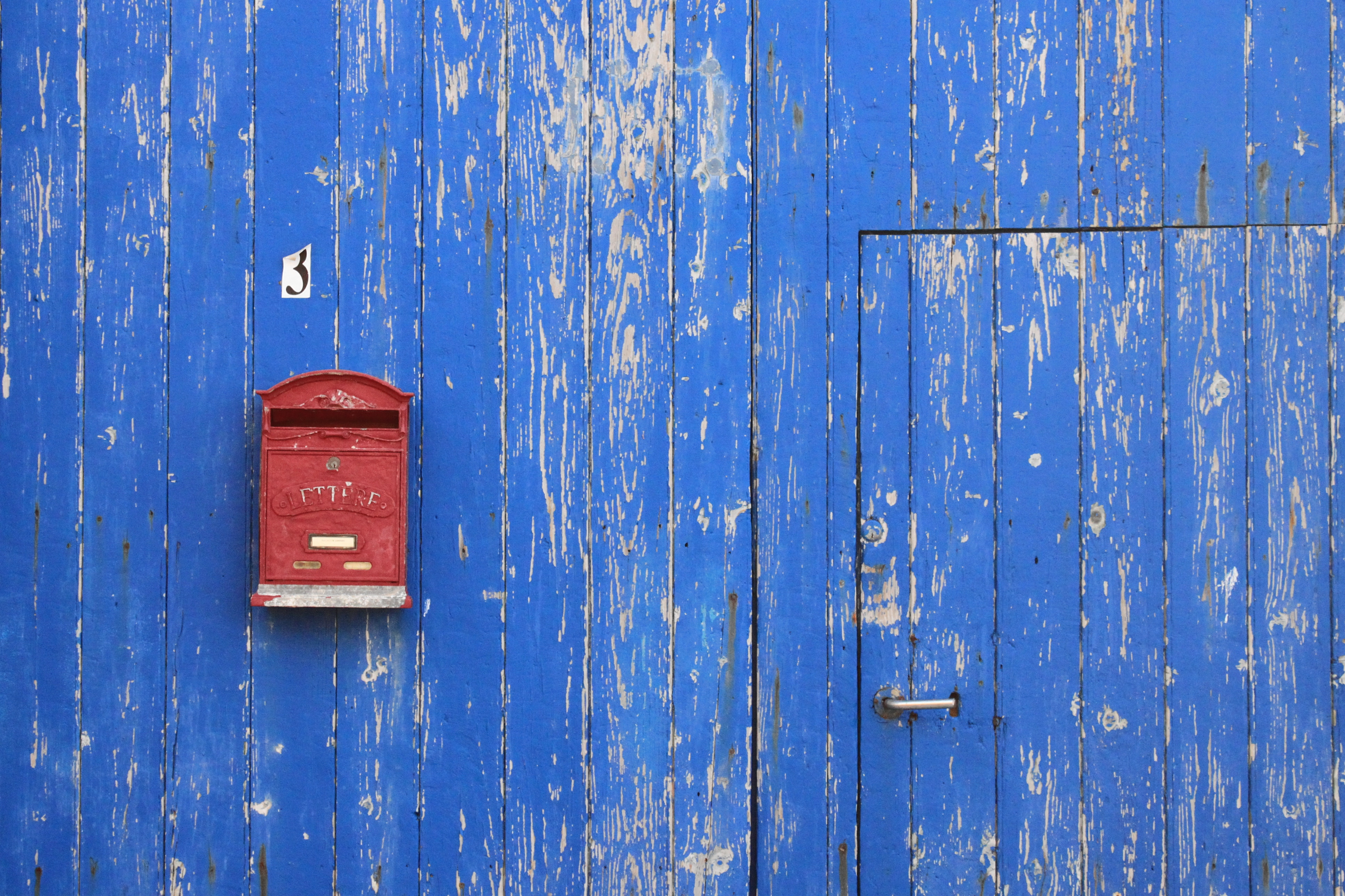 red mailbox on blue wall